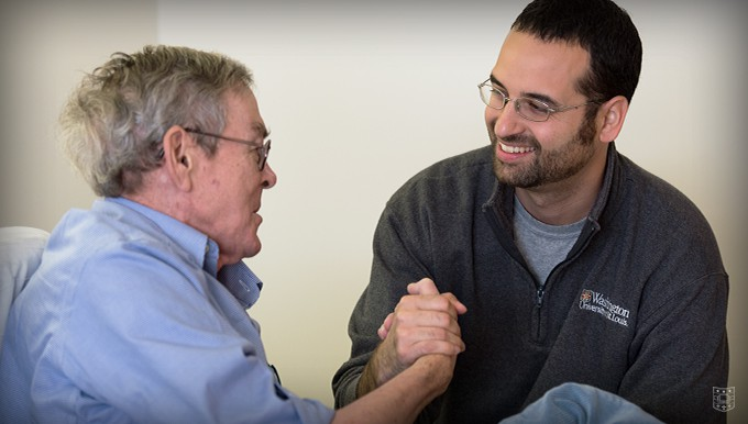 "Mike Pereira (right), a University College student and Army veteran, visits with Navy veteran John ""Mike"" Kenny at the VA Medical Center in St. Louis. Pereira has worked with hospice patients since 2012. Photo by Joe Angeles/WUSTL Photos"
