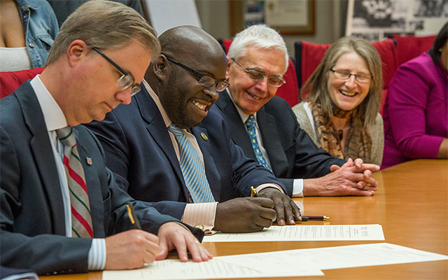 Provost Holden Thorp, PhD (left), and Dwyane Smith, PhD, provost and vice president for academic affairs at Harris-Stowe State University, sign an agreement to create a partnership between the two institutions. Looking on are Ralph S. Quatrano, PhD, dean of the School of Engineering & Applied Science at Washington University, and Ann Podleski, PhD, professor of mathematics at Harris-Stowe. Joe Angeles/WUSTL Photos