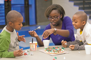 Junior Gloria Osei (center) helps Brandon Garrison, 7, (left) and Zacharia Berry, 8, decorate a cookie during the Each One Teach One celebration Sunday, Dec. 7, 2008, at the Gargoyle. Photo by Whitney Curtis